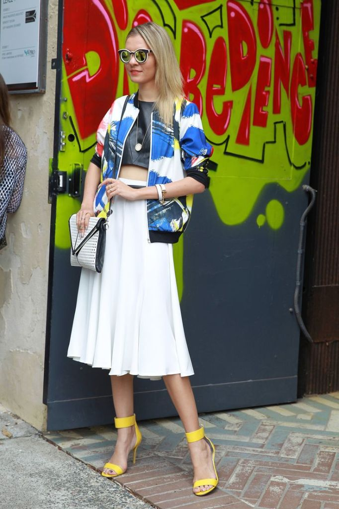 white pleated midi skirt, artsy printed bomber baseball jacket, leather crop top, yellow heels, sunglasess, spring outfits