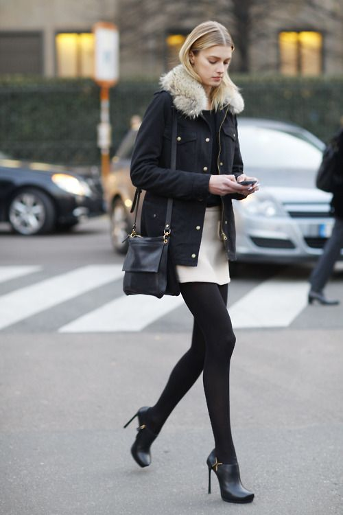 white skirts in winter, white mini skirt, black and white outfit, black tights, holiday outfit, winter work outfit, black fur trimmed parka jacket, black booties, mini skirts in winter