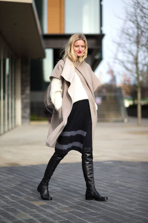 how to wear over the knee boots, spring-work-black-skirt-knit-skirt-white-sweater-black-over-the-knee-boots-camel-coat-short-sleeve-coat-candice-lake-blogger-via-hbz
