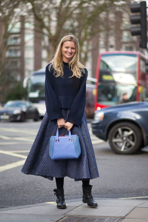 work-midi-skirt-spring-moto-boots-boxy-sweater-navy-pastel-blue-bag-candice-lake-via-hbz