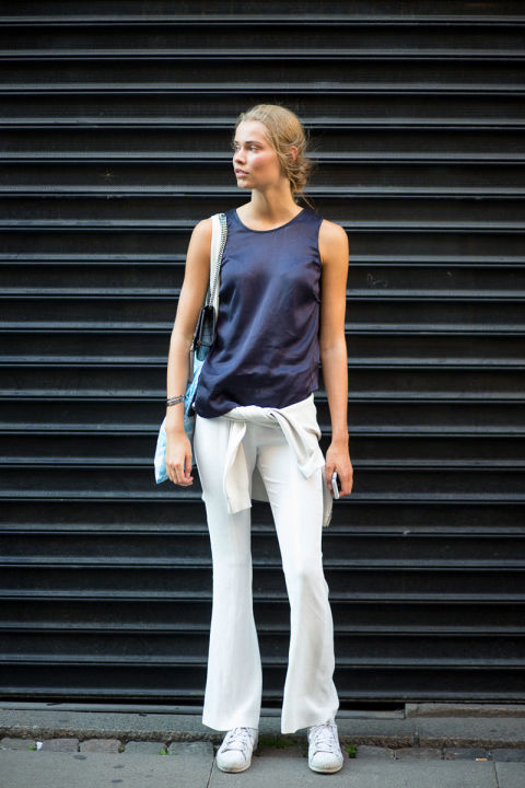 white jeans-navy-shirt around waist-sneakers-summer weekend outfit-weekend-hbz