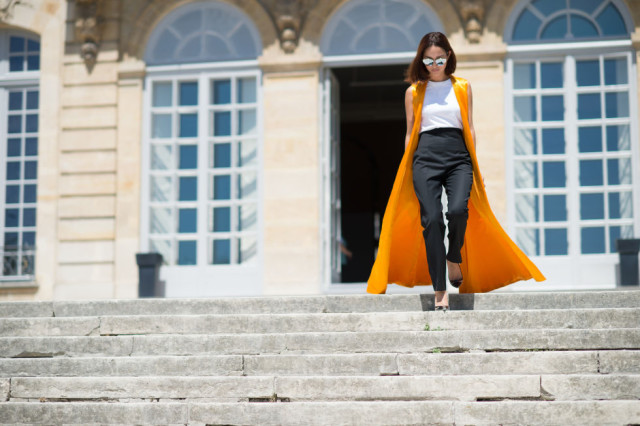 black-trousers-black-and-white-summer-work-otutfit-yellow-orange-vest-paris-couture-fashion-week-street-style-via-elle.com
