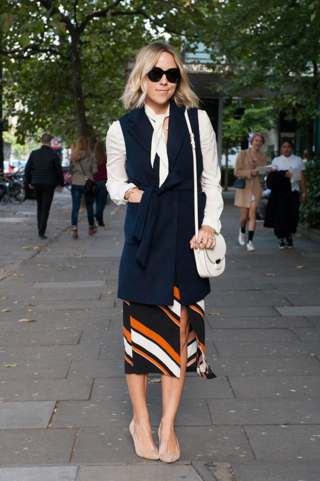 bow blouse-sleeveless vest-navy vest-striped-skirt-fall colors-orange-white bag-fall work outfit-lfw-fall fashion-london fashion week street style-via-popsugar
