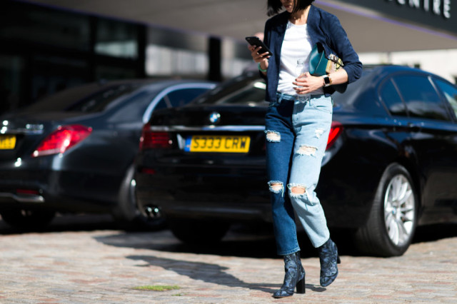 distressed ripped mom jeans-mismatched leg jeans-cropped jeans and booties boots-whtie tee-fall jacket-lfw street style-elle.com