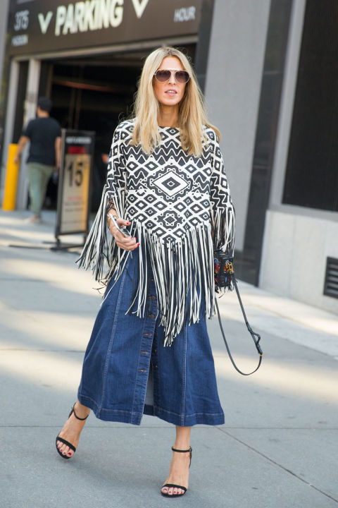 button front denim skirt, 70s trend, fringe poncho, midi skirt, simple black heels, nyfw street style via elle.com