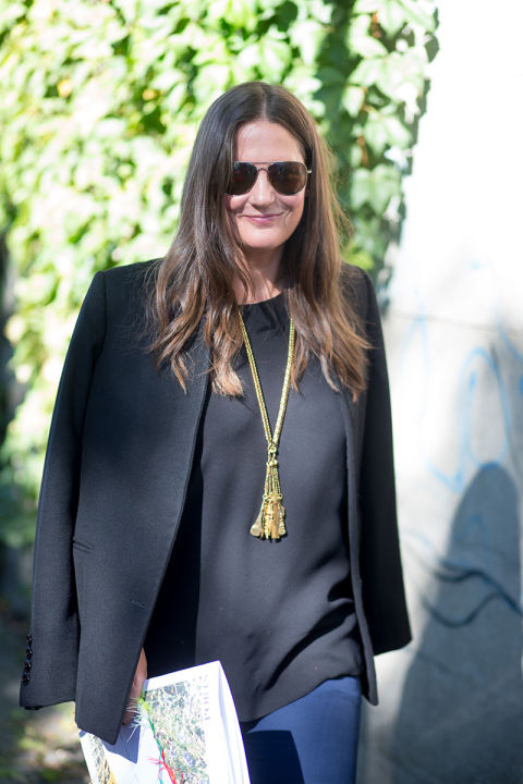 fringe pendant necklace-black jacket on shoulders-jeans-black outfit-milan fashion week street style-via hbz