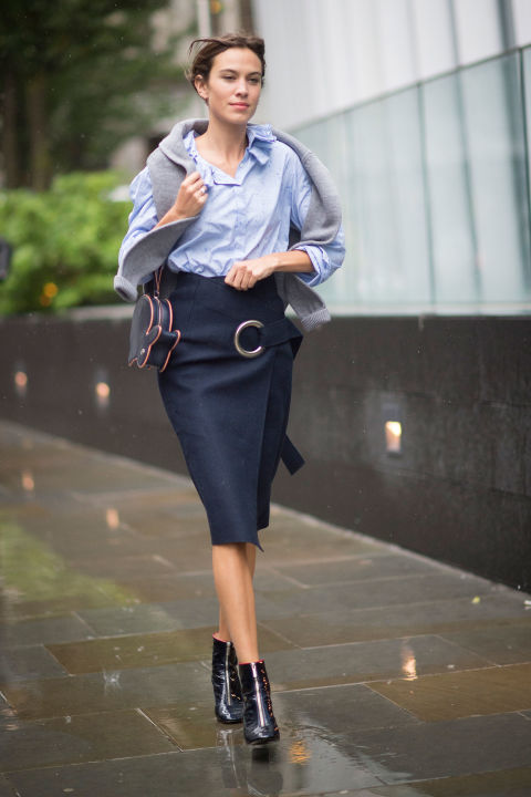 lfw street style fall style alexa chung wrap skirt oxford shirt fish purse sweater over shoulders black booties fall work outfit