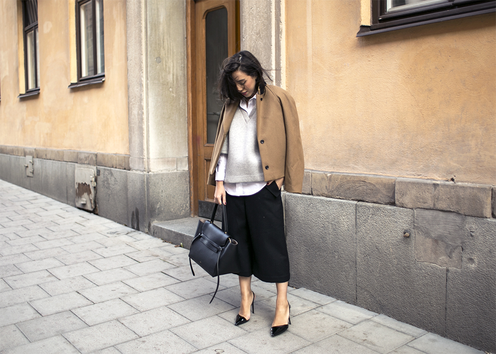 fall layers fall work outfit black culottes cutout pumps pointy toe black pumps white oxford shirt grey cropped sweater jacket on shoulders fall layers camel coat jacket on shoulders via sania clau demina