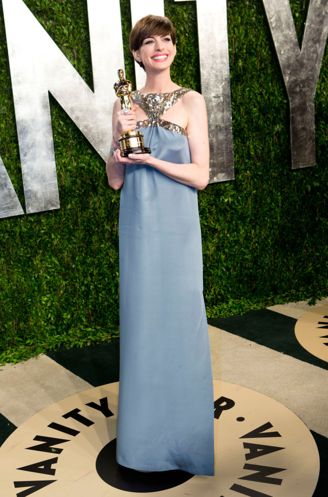 Anne Hathaway carrying her Oscar for best supporting actress arrives for the 2013 Vanity Fair Oscar Party on February 24, 2013 in Hollywood, California. AFP PHOTO / ADRIAN SANCHEZ-GONZALEZ (Photo credit should read ADRIAN SANCHEZ-GONZALEZ/AFP/Getty Images)