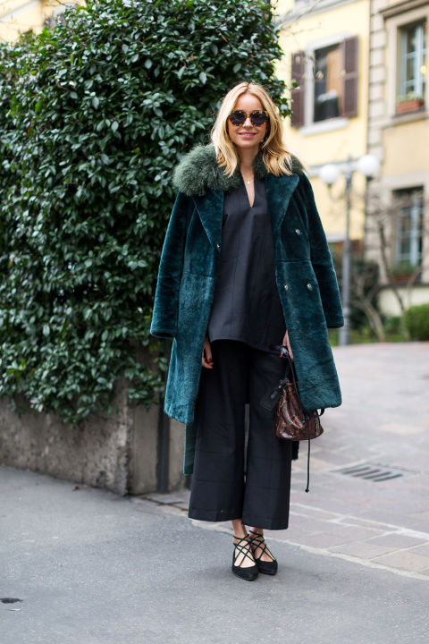 emerald green fur coat-lace up ballet lflats-black tunic-black culottes-all black-winter to spring transitional dressing-milan fashion week-hbz