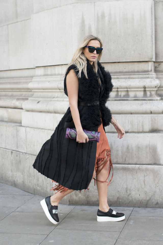 sleeveless vest-sleeveless coat-fringe skirt-platform sneakers-platform slip on shoes-fur vest-belted fur -lfw street style-psuk-getty